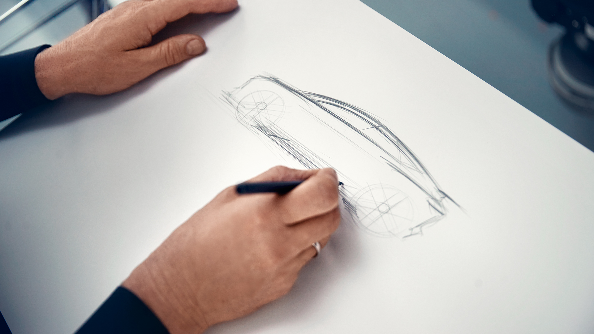 Oblikovalec skicira konceptno vozilo.