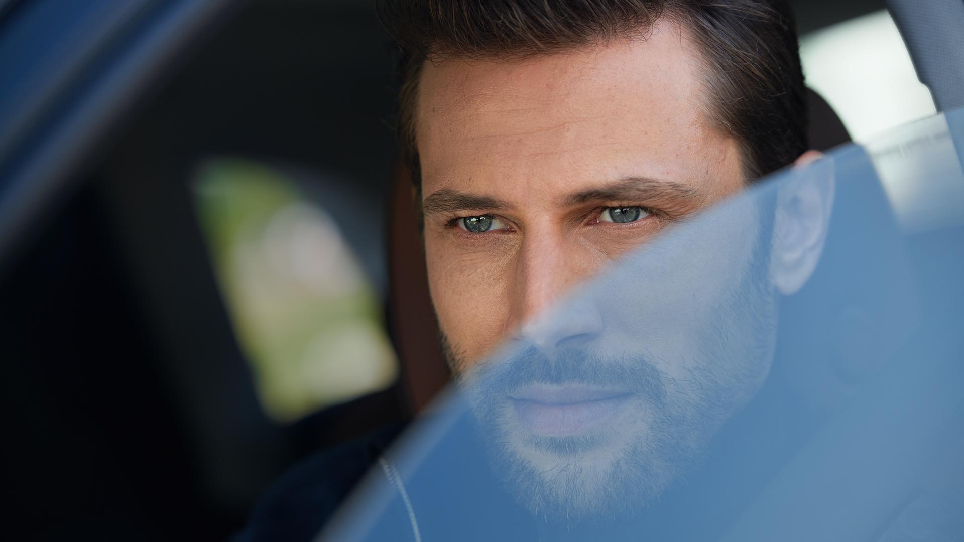 Moški gleda skozi okno avtomobila.