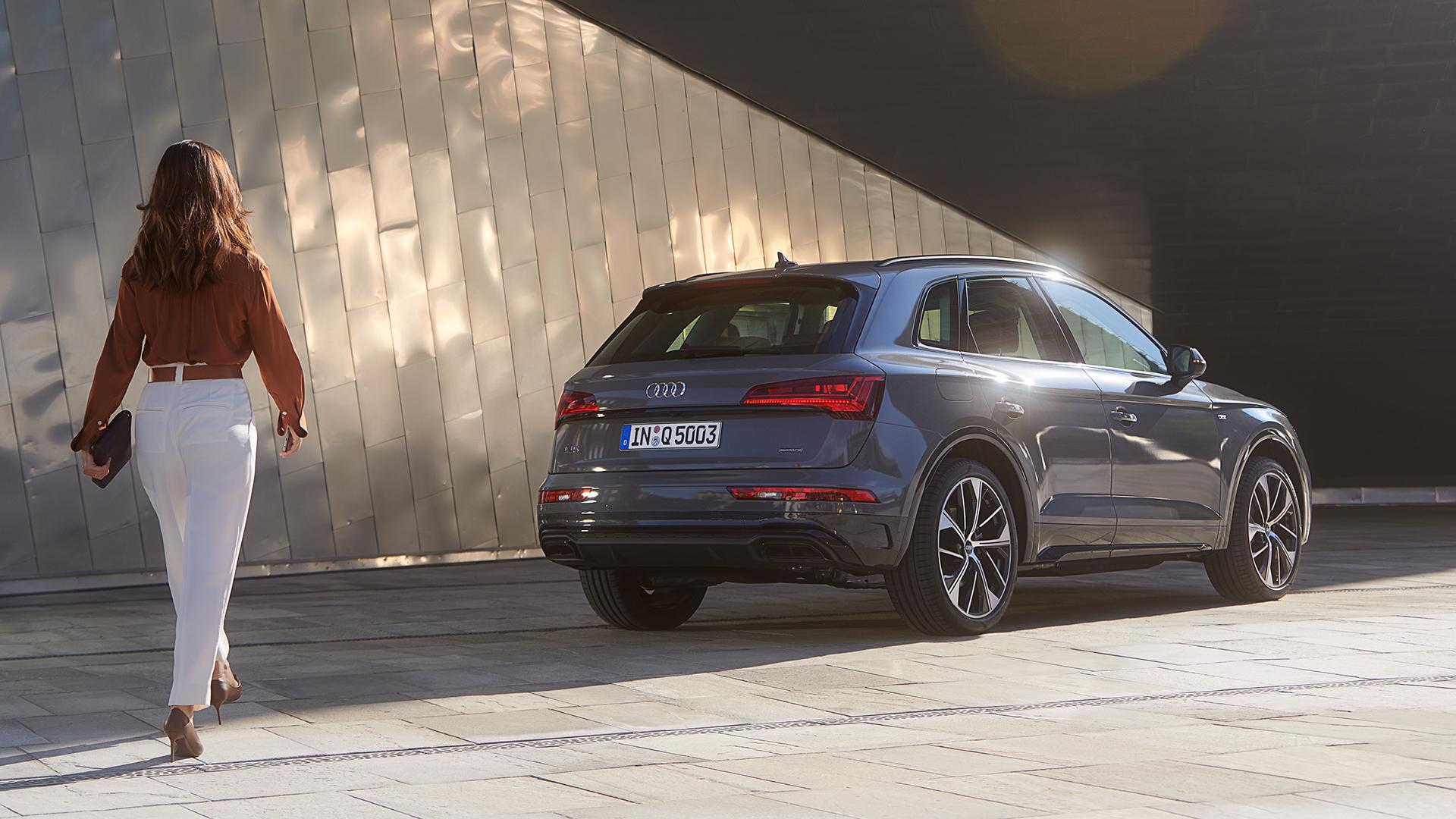Ženska se približuje parkiranemu Audiju Q5 SUV v kvantno sivi barvi.