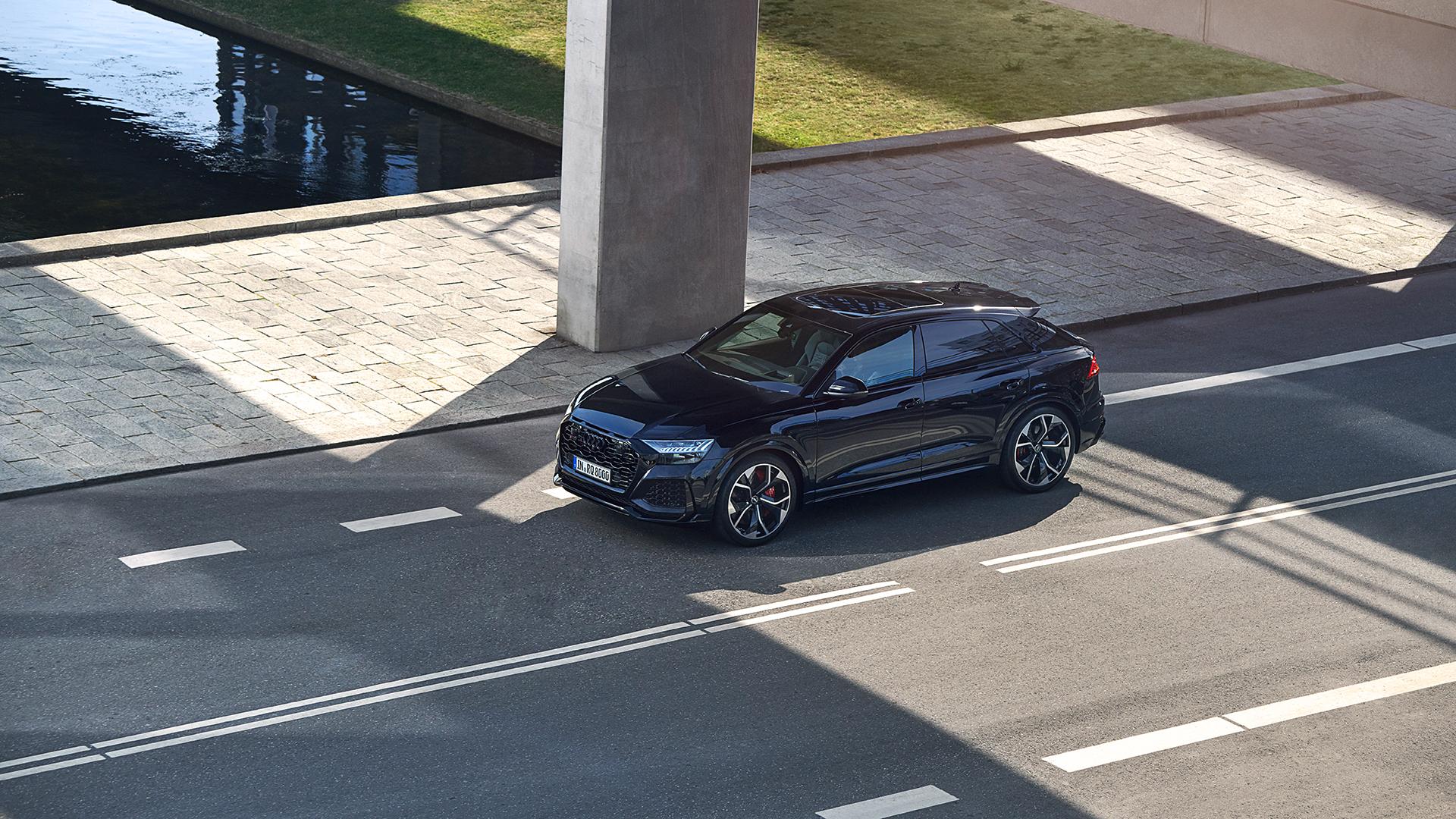Audi RS Q8 športne orka-črne barve na ulici.