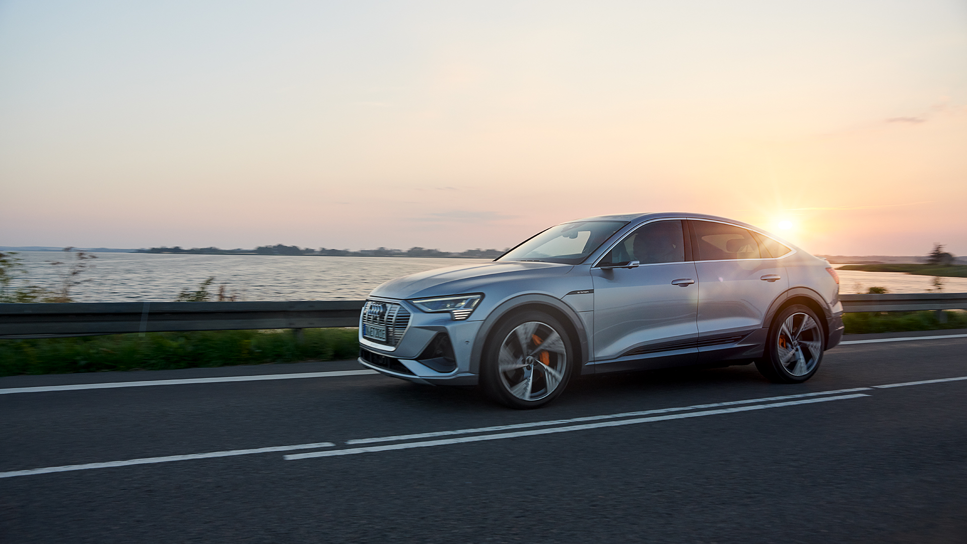 Florett srebrn Audi e-tron Sportback SUV coupé na avtocesti v jutranji zori.